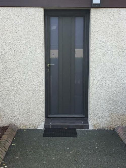 Porte d''arrière cour dans une maison à Plérin. La porte est en aluminium, de couleur gris anthracite, et en verre brossé pour une entrée de lumière tout en protégeant votre intimité.