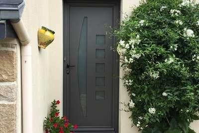 Une porte entrée en alu de type voile à Saint-Brieuc, par Costa Menuiseries. Elle dispose de parties vitrées carrées et oblongues, pour donner un style contemporain.
