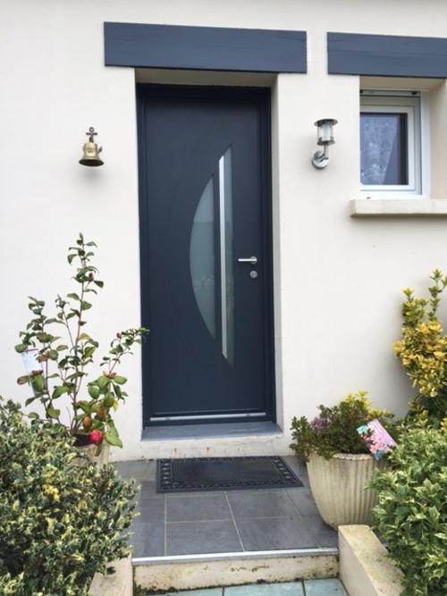 Porte d''entrée en aluminium avec vitrage dépoli en demi-lune. Visible à Ploufragan, conçue et posée par l''équipe de Costa Menuiseries.