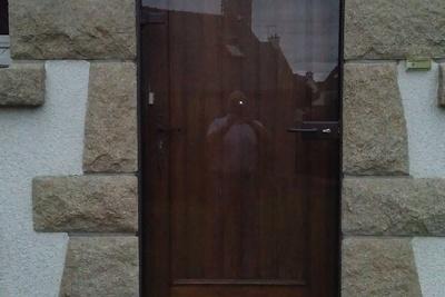 Porte d''entrée atypique d''une maison néo bretonne. La porte est en bois et est protégées par un doublage vitré.