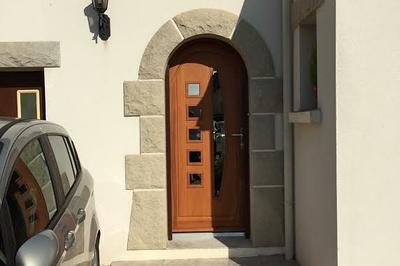 Porte d''entrée d''une maison néo bretonne à Yffiniac. Parties vitrées carrées et oblongues pour faire entrer la lumière. Choix d''un thermolaquage couleur bois pour appuyer le côté chaleureux et traditionnel.
