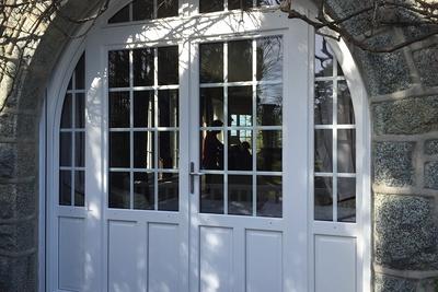Magnifique porte fenêtre à double battant. Vitrage petit carreaux et imposte pour un aspect traditionnel. Cintrage bois et couleur blanche.