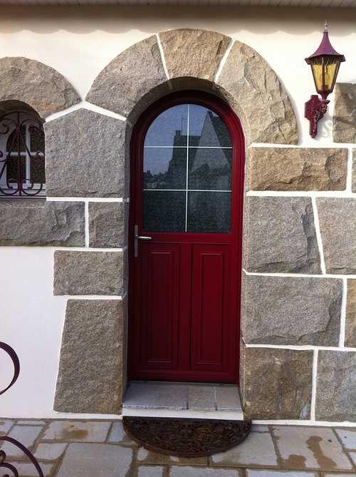 Porte d''entrée mixte alu et bois rouge à Trégueux. Plein cintre avec une partie vitrée pour plus de luminosité.