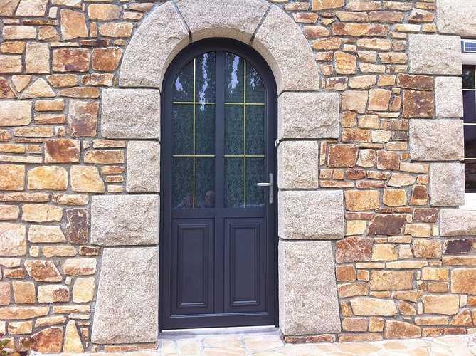 Porte d''entrée gris anthracite plein cintre. Mixte alu/bois avec vitrage dépoli. Habille une maison bretonne à Plouvara, dans les Côtes d''Armor